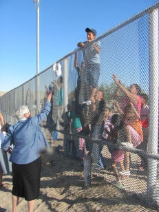 NUN TOSSES HATS OVER FENCE TO PEOPLE AT U.S. MEXICO BORDER